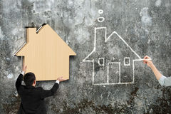 Équipez mettre la maison en bois dans le trou du mur en béton Photographie stock
