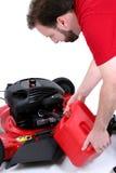 Équipez mettre le gaz dans la tondeuse à gazon au-dessus du blanc Images stock