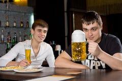 Équipez observer une grande chope de bière d'avance Image stock