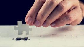 Équipez placer le dernier morceau dans le puzzle denteux Photo libre de droits