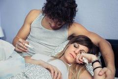 Équipez regarder la température de la femme malade dans le thermomètre Photo libre de droits