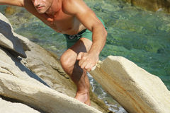 Équipez s'élever sur des roches de montagne contre l'eau de mer Sports extrêmes dehors Vacances d'été actives Images libres de droits