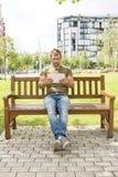 Équipez se reposer sur le banc et tenir la tablette dans la rue Photographie stock libre de droits