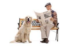 Équipez se reposer sur un banc avec son chien et la lecture Image stock