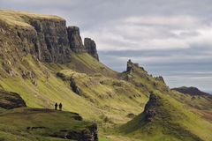 Quiraing,斯凯岛,苏格兰-与站立两个人的图的异常的岩石风景小岛在前景的峭壁 免版税库存图片
