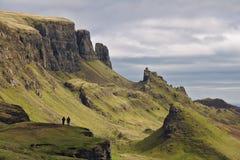 Quiraing ö av Skye, Skottland - bisarrt stenigt landskap med två mänskliga diagram som står på en klippa i förgrunden royaltyfria bilder