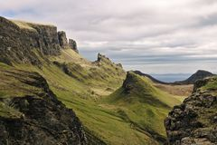 Quiraing, wyspa Skye, Szkocja - Dziwaczny skalisty krajobraz zakrywający z zieloną trawą z dwa skalistymi falezami w przedpolu Obraz Royalty Free