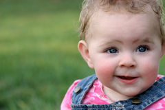 Quirky Grin. Baby girl's quirky grin royalty free stock photos