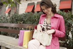 Quirky Woman With Shopping. Young woman searching through her purse while sitting down with shopping bags Stock Images