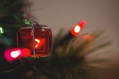 Quirlande électrique et petit boîte-cadeau accrochant sur l'arbre de Noël Photo stock