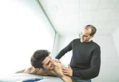 Quiropráctico que da masajes a un hombro del hombre joven Concepto de fisioterapia imagen de archivo
