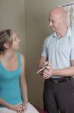 Quiroprático ocupado com da mostra a espinha paciente dorsal Imagem de Stock Royalty Free