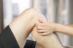 Quiroprático /physiotherapist que faz uma massagem do joelho fotografia de stock