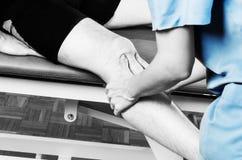 Quiroprático /physiotherapist que faz uma massagem do joelho na silhueta foto de stock royalty free