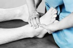 Quiroprático /physiotherapist que faz uma massagem dos pés no silhouet foto de stock