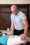 Quiroprático que ajusta o quadril e o pé pacientes Fotos de Stock Royalty Free