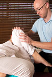 Quiroprático que ajusta os músculos do pé com exercício Imagens de Stock Royalty Free
