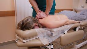 Quiroprático que faz massagens uma jovem mulher que encontra-se em uma tabela da massagem, empurrando nela para trás com seus cot fotos de stock royalty free