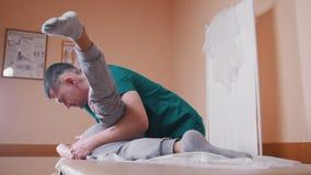 Quiroprático que faz massagens uma jovem mulher que encontra-se em uma tabela da massagem, esticando e dobrando sua articulação d video estoque