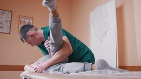 Quiroprático que faz massagens uma jovem mulher que encontra-se em uma tabela da massagem, esticando e dobrando sua articulação d filme