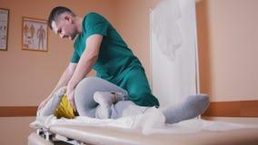 Quiroprático que faz massagens uma jovem mulher que encontra-se em uma tabela da massagem, esticando e dobrando suas articulação  vídeos de arquivo