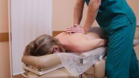 Quiroprático que faz massagens uma mulher que encontra-se em uma tabela da massagem, dobrando o ombro fotos de stock royalty free
