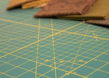 Quit rotary cutting mat with brown fabric in background Royalty Free Stock Photo