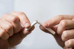 Quit fumant, mains humaines cassant la cigarette photo libre de droits