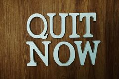 Quit Now word alphabet letters on wooden background. Top View of Quit Now word alphabet letters on wooden background stock photo