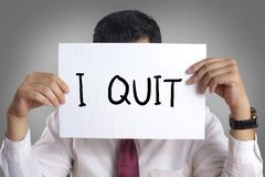 Quit Resign Employee Concept. Businessman hiding his face behind paper with I quit words written on it, resign employee concept message quitting communication stock images