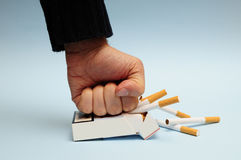 Quit smoking. Man hand crushing a packet of cigarettes, quit smoking resolution Stock Image