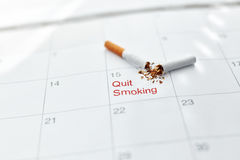 Quit Smoking. Close Up Of Broken Cigarette Lying On Calendar stock photography