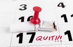 Quit Smoking Date. Quit smoking deadline with cifarette butts nailed with red pin to calendar Stock Image