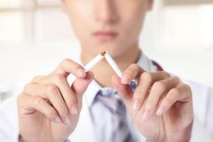 Quit smoking. Doctor hands breaking the cigarette, close up, asian model royalty free stock photos