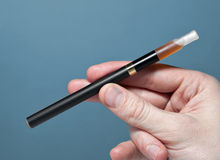 Quit smoking with electronic cigarette. Black electronic cigarette (510 T) with refillable tank held in male hand. Aid to help quit smoking Royalty Free Stock Photo