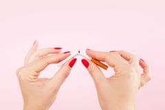 Quit smoking resolution. Female hands with red fingernails braking the last cigarette isolated on pink background. Quit smoking new year resolution royalty free stock photos
