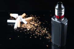 Quit smoking and start vaping. Pile of broken cigarettes with modern electronic cigarette Stock Photography