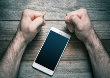 Quit Using Smartphone Or Social Media Concept With A White Mobile Phone Surrounded By 2 Stressed Looking Clenched Fists. A Quit Using Smartphone Or Social Media royalty free stock photos
