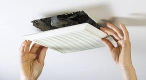 Quitando la cubierta del respiradero de la fan del cuarto de baño para limpiar dentro foto de archivo
