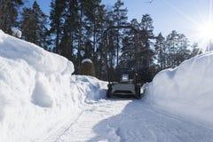 Quitanieves en el trabajo sobre un día de invierno Quitanieves que quita nieve después de ventisca Vaciamiento del hielo Máquina  Imagen de archivo libre de regalías
