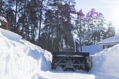 Quitanieves en el trabajo sobre un día de invierno Quitanieves que quita nieve después de ventisca Vaciamiento del hielo Máquina  Foto de archivo libre de regalías