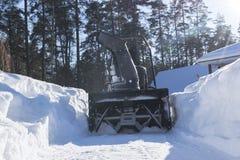 Quitanieves en el trabajo sobre un día de invierno Quitanieves que quita nieve después de ventisca Vaciamiento del hielo Máquina  Fotografía de archivo
