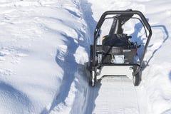 Quitanieves en el trabajo sobre un día de invierno Quitanieves que quita nieve después de ventisca Vaciamiento del hielo Máquina  Imagen de archivo