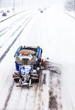 Quitanieves que quita la nieve de la carretera durante una nevada Foto de archivo libre de regalías