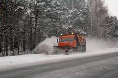 Quitanieves que quita nieve del camino interurbano Fotografía de archivo