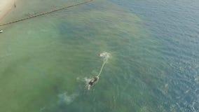 ?quitation de jeune homme sur le panneau de mouche avec le jet de jet d'eau au-dessus de l'eau de mer bleue Cavalier de panneau d banque de vidéos