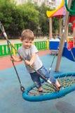 Équitation de quatre ans d'enfant se tenant sur l'oscillation ronde Photographie stock