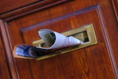 Fresh news, newspaper at door. Quite close up photo of a classic indoor mailbox with some fresh newspaper. You may see traditional way of news delivery. Paper stock photos