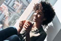 Quite contemplation. Attractive young African woman holding a cup and smiling while sitting on window sill indoors stock photo