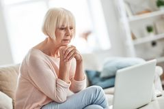 Quite contemplation. Beautiful senior woman keeping hands clasped and thinking about something while relaxing on the couch at home royalty free stock photography